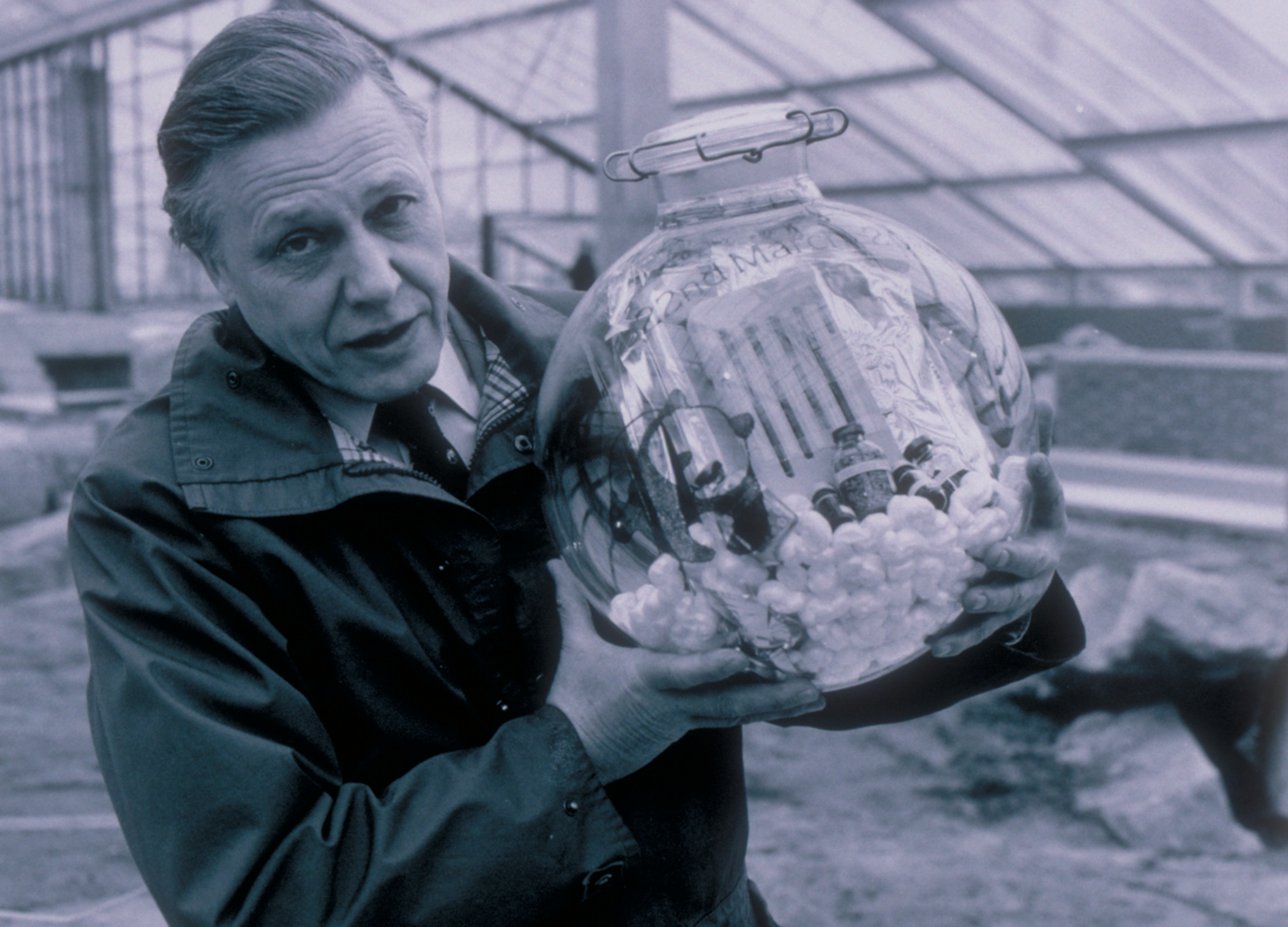 David Attenborough holding a time capsule before it was buried in the foundations of the Princess of Wales Conservatory