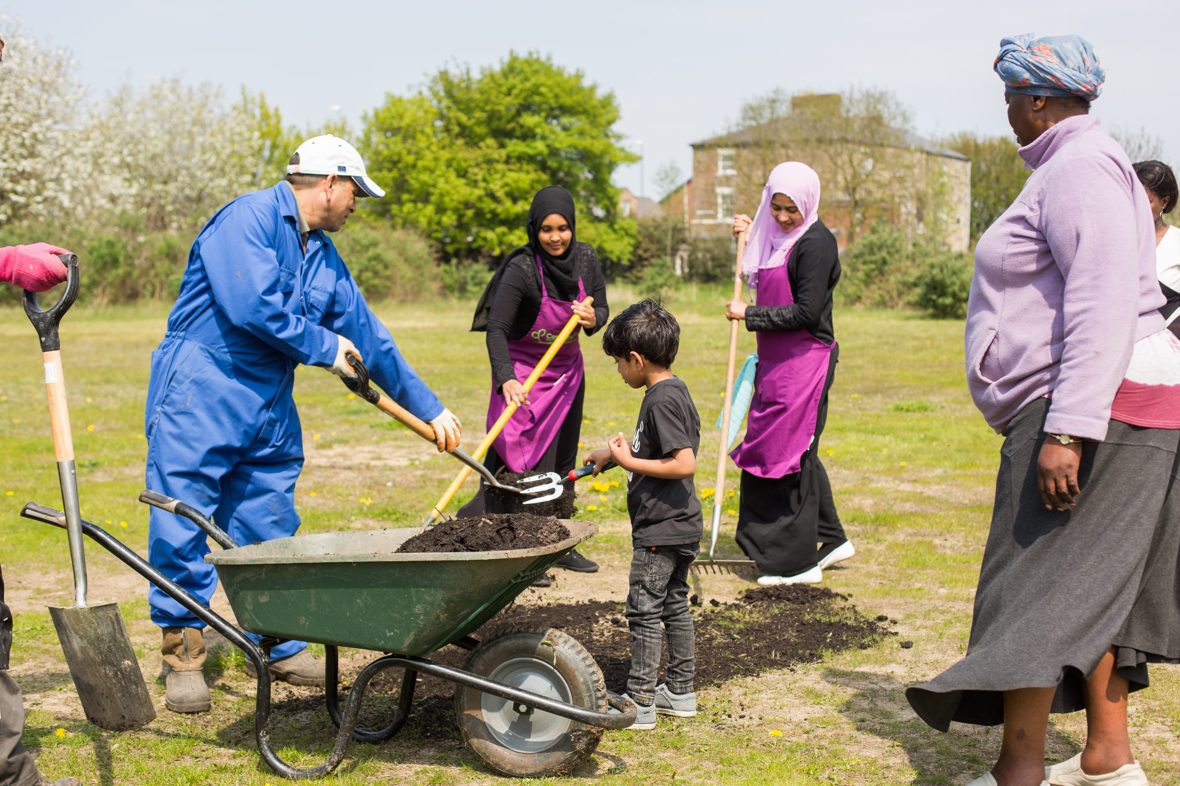 Women and children take part in an outreach project,putting soil into a wheelbarrow
