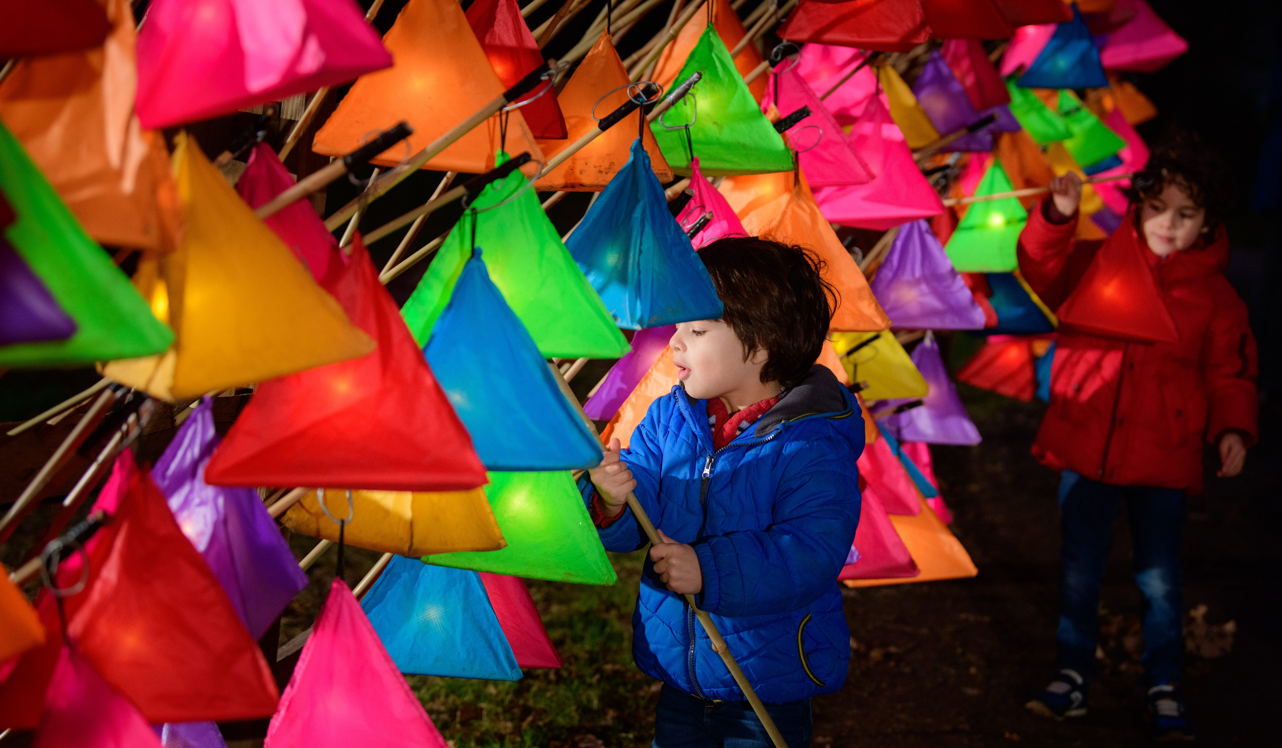 Children picking up Glow Wild hand-held lanterns