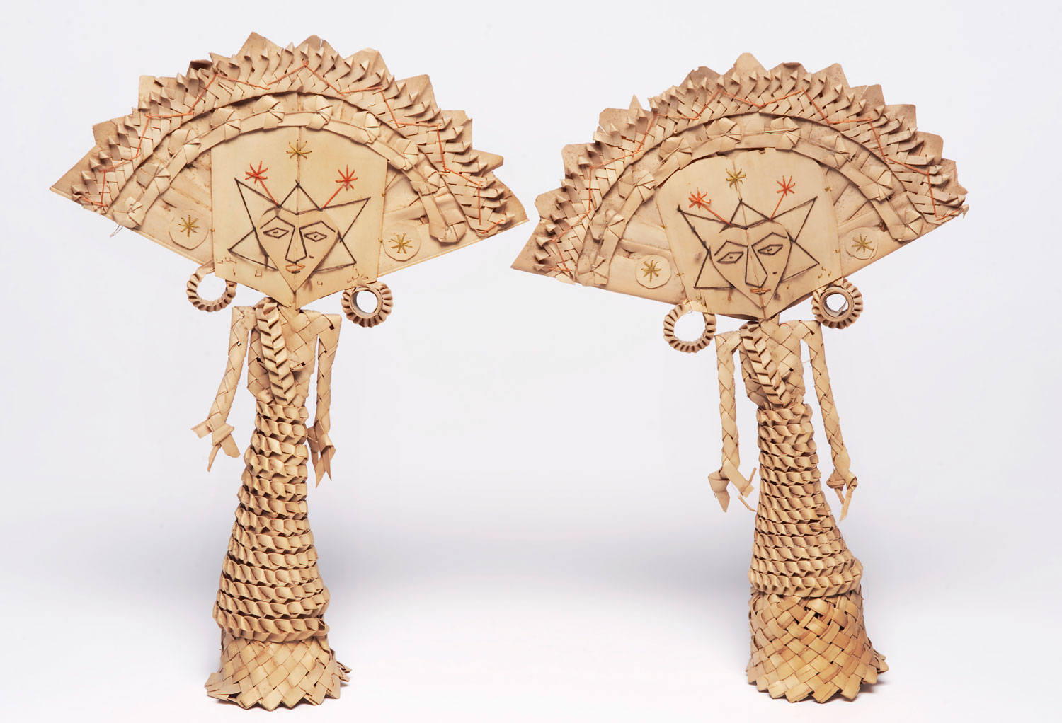 Two dolls made from palm leaves with a fan shaped head