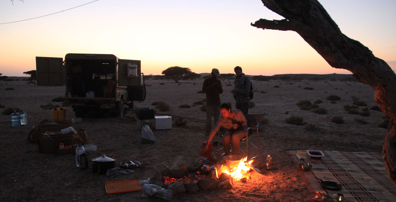 Dusk in the Oman desert with the researchers by a fire