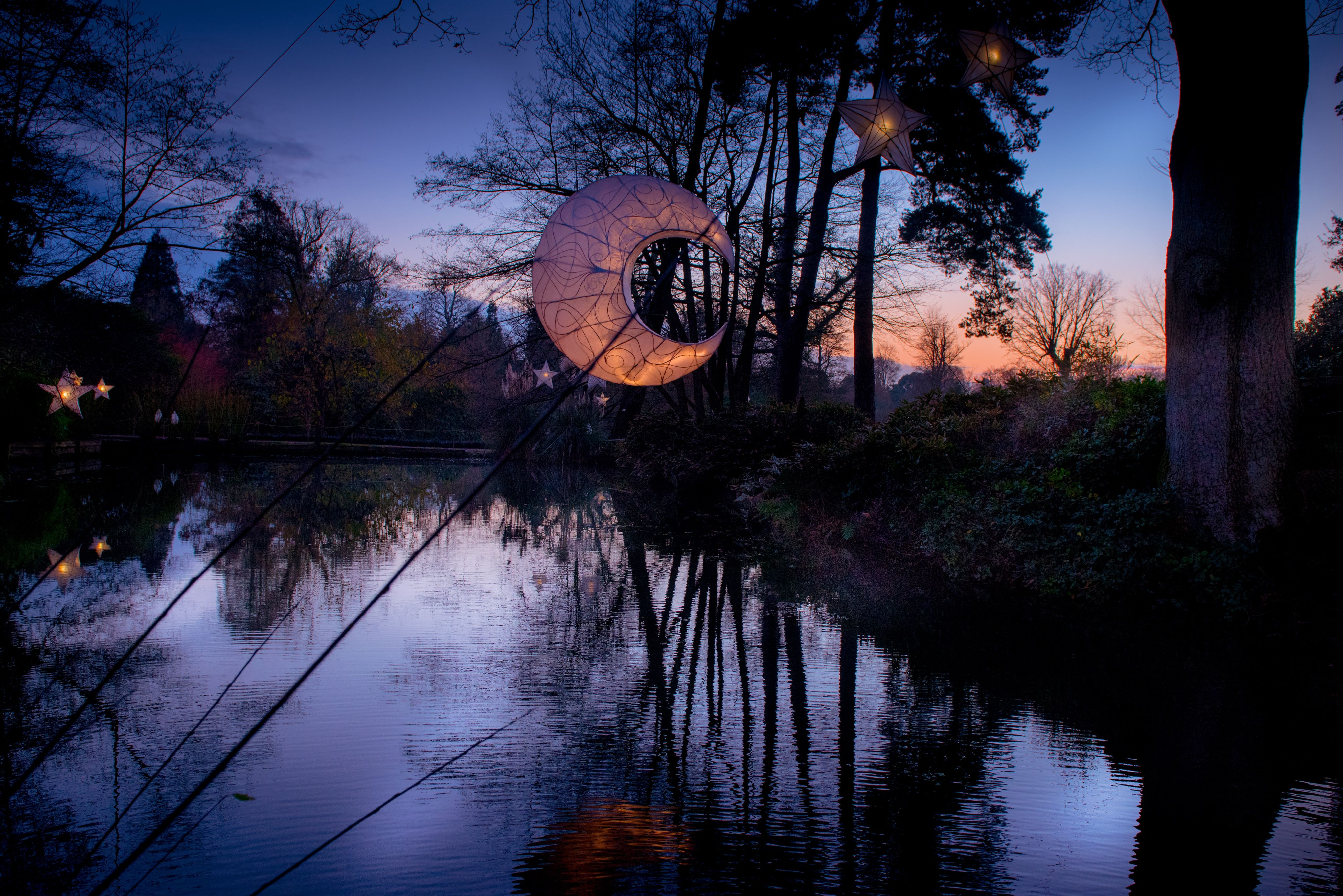 Moon lantern hanging over the Black Pond at Wakehurst during the Glow Wild festival