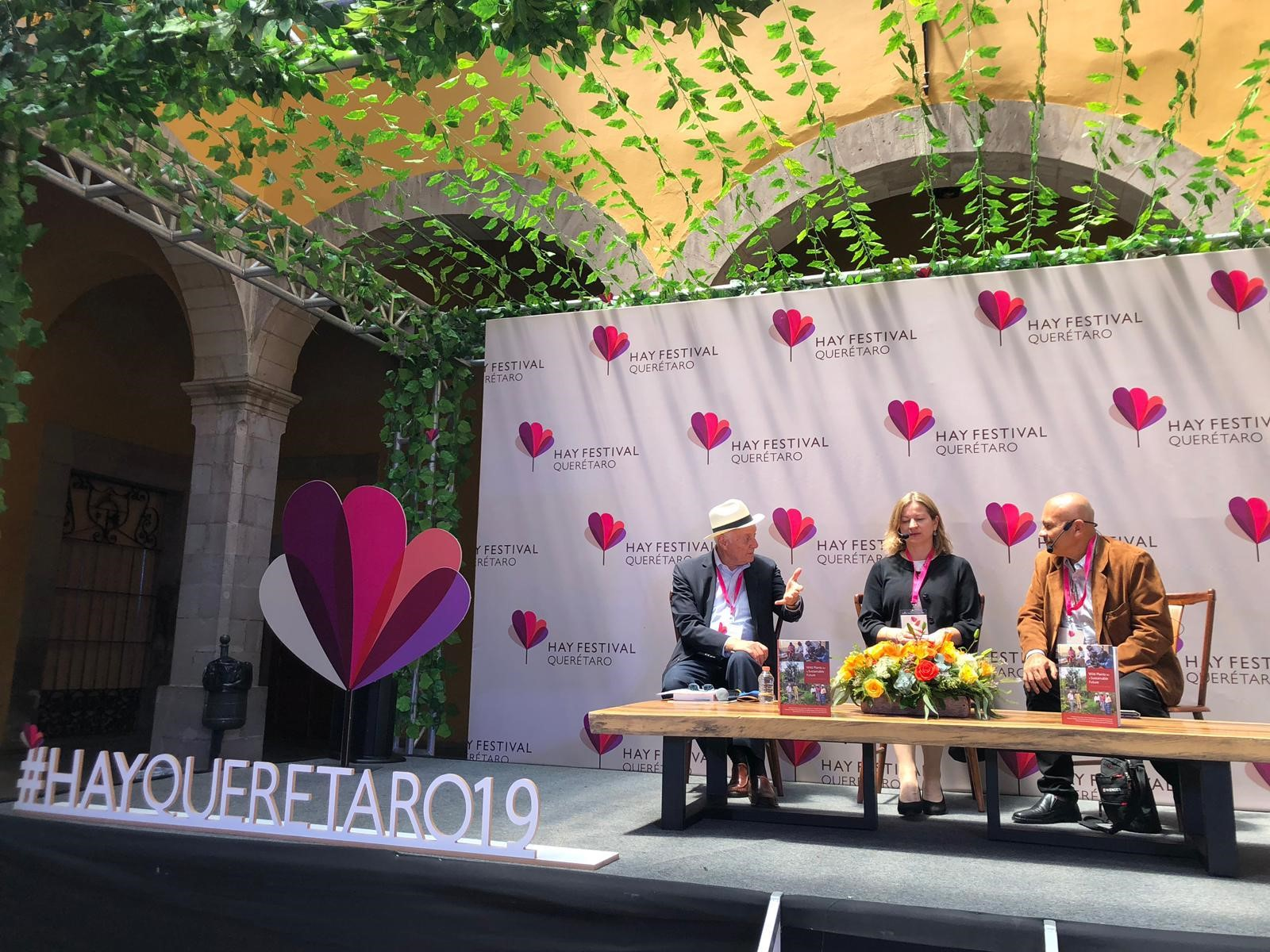 Tiziana on stage in front of Hay Festival backdrop with Andres ad Rafael