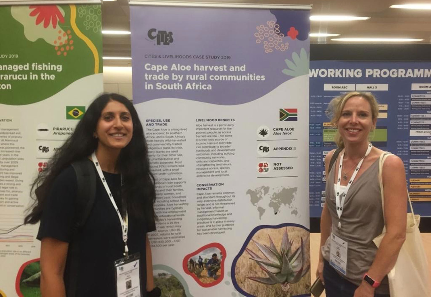 Sonia and Carly stood in front of poster at the conference