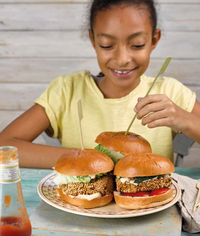 A young girl inspects a plate of bean burgers