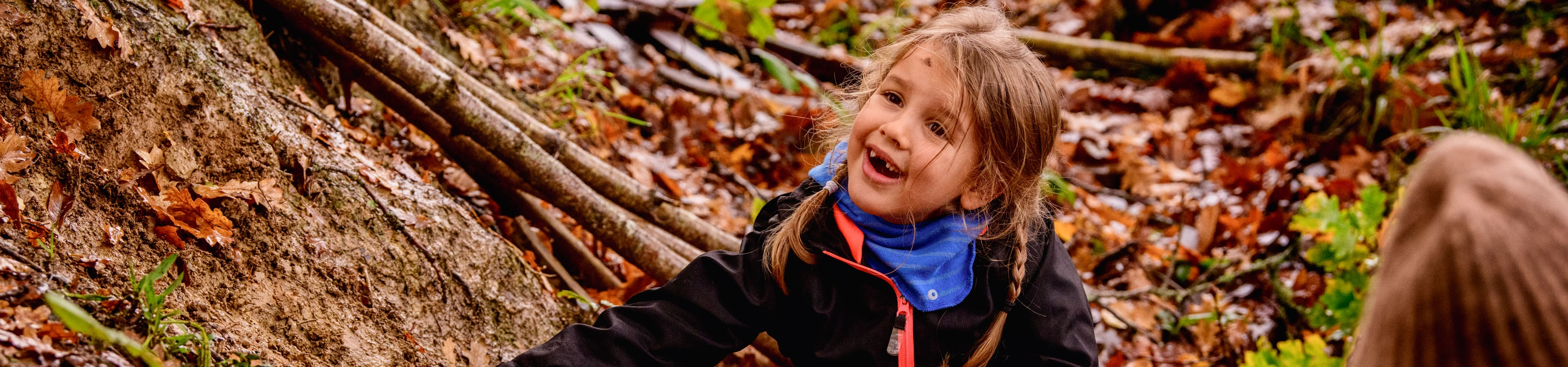 A young girl smiles and plays on the forest floor of Wakehurst