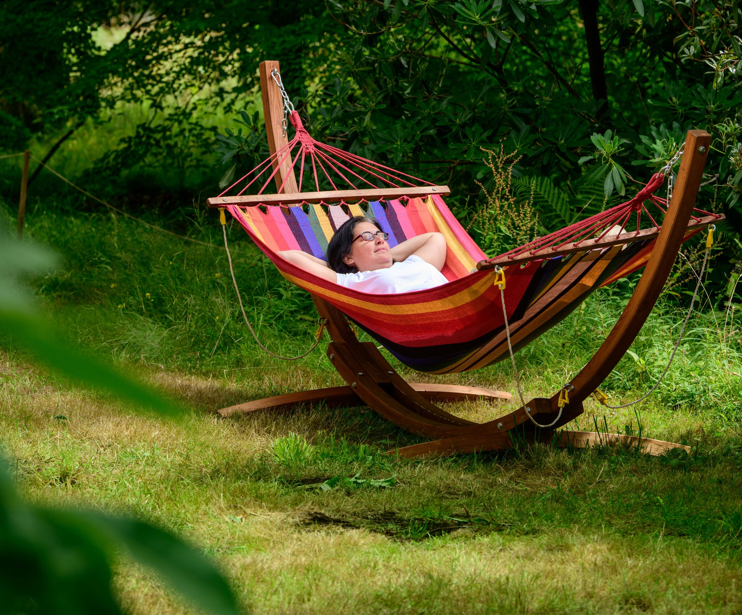 A woman lays in a colourful hammock amongst a forest glade
