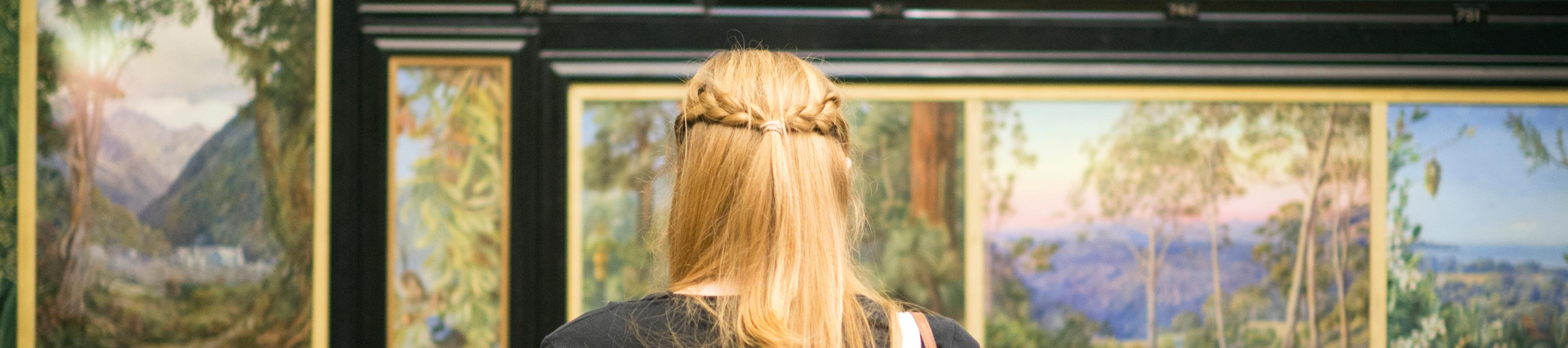 The back of a woman's head as she takes in the paintings at the Marianne North gallery