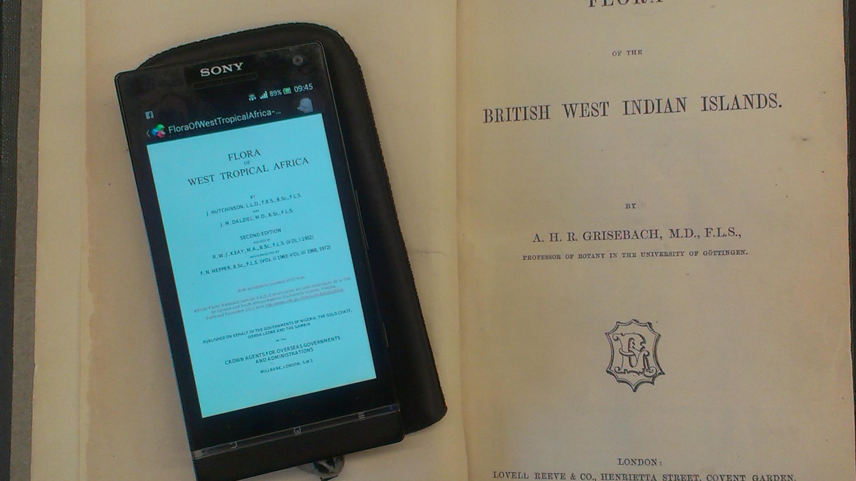 A picture showing the eBook Flora of West Tropical Africa on a mobile phone alongside an old volume of the Flora of the British West Indies
