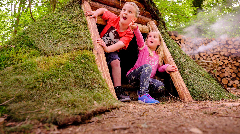 Children in woodland den at Wakehurst