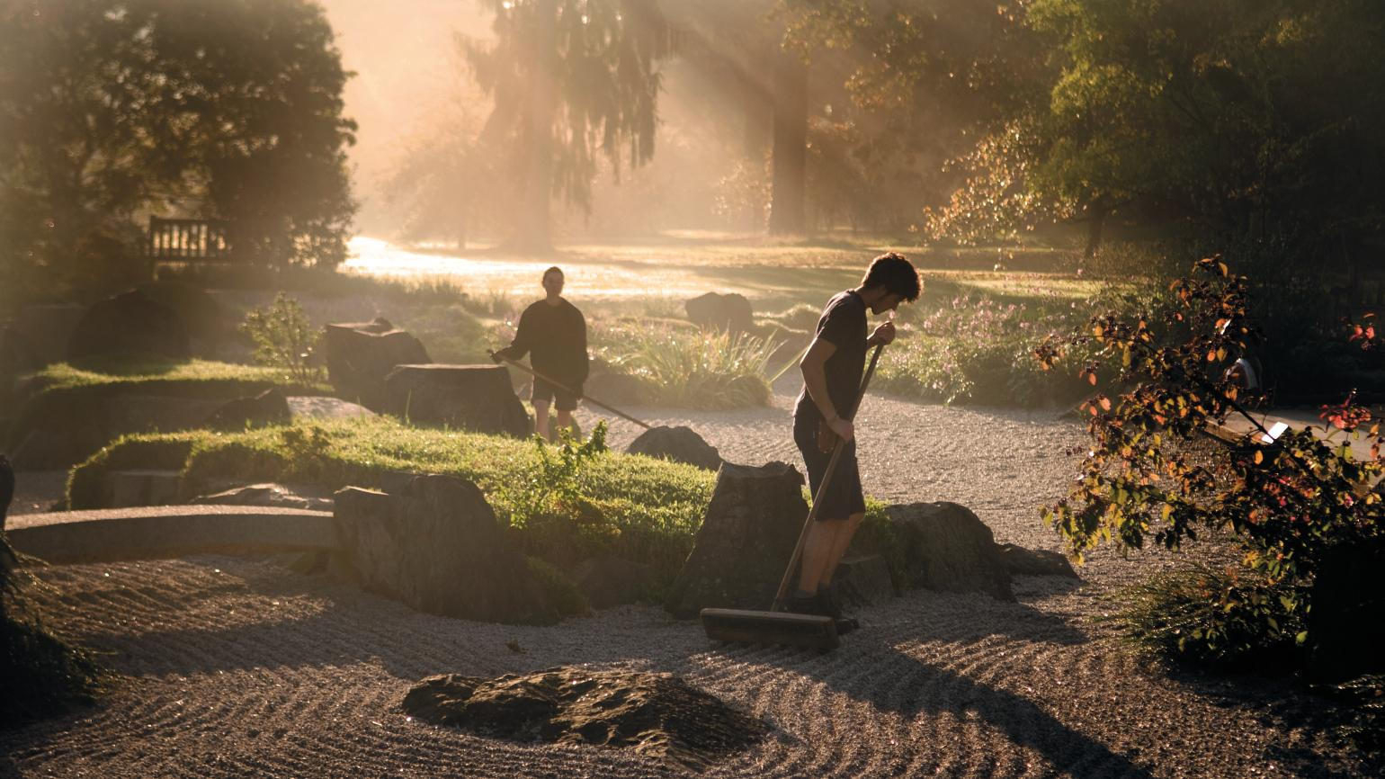 Horticulturists raking the gravel in the Japanese Landscape at Kew