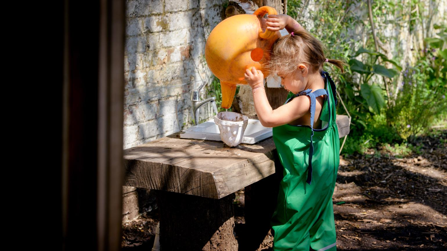A child playing in the Mud Kitchen at Wakehurst