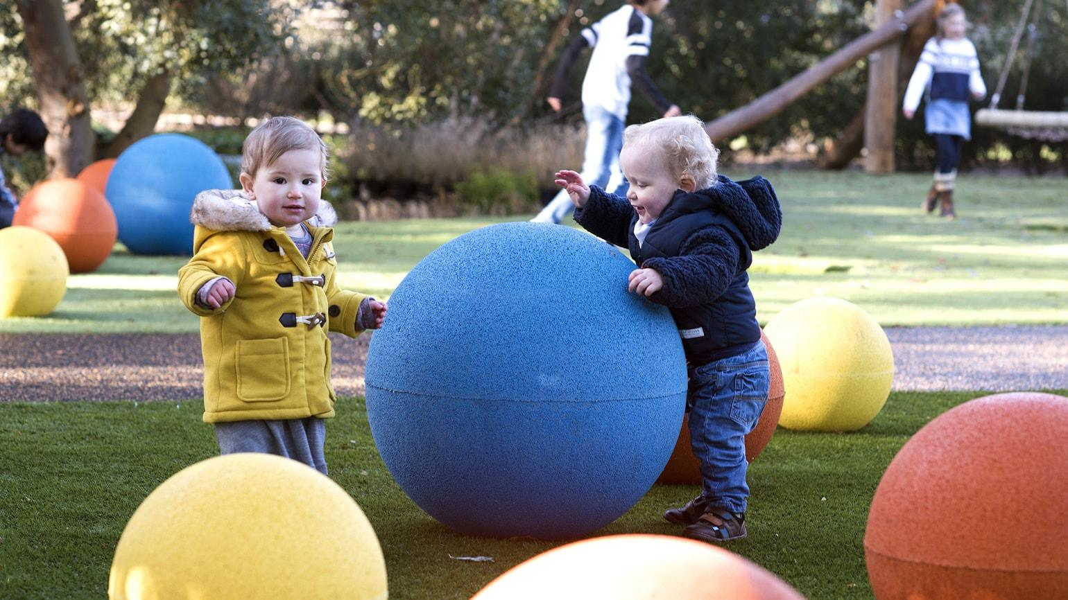 Toddlers play on giant coloured balls in the Children's Garden