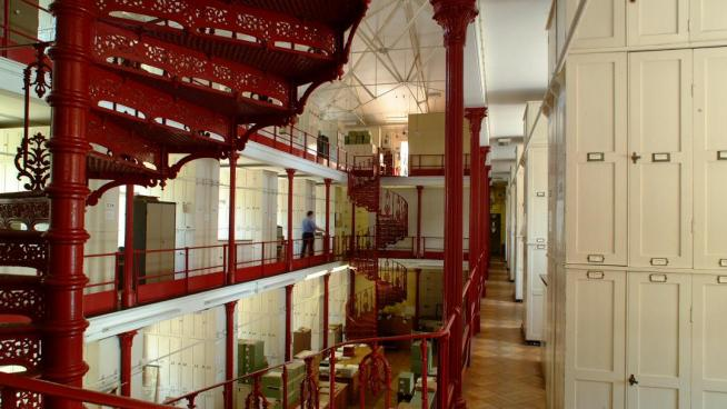 The red cast-iron pillars and spiral staircases inside Kew's Herbarium