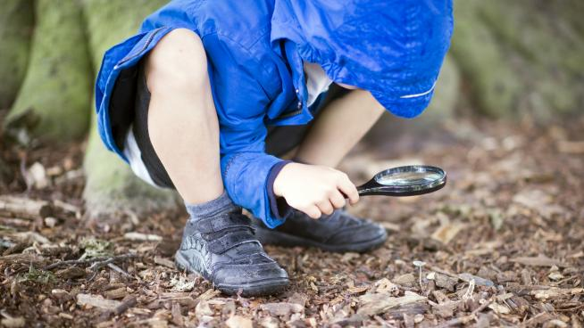 Child using magnifying glass