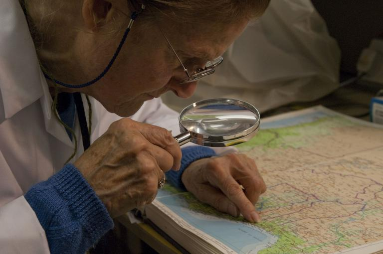 Hazel studying a map while working on Adam's case