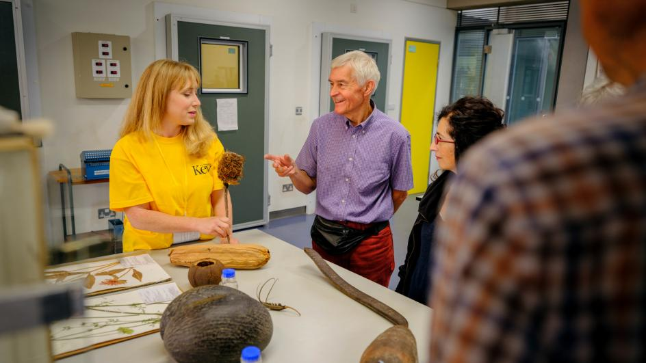 Staff in yellow t-shirts discuss their work with visitors