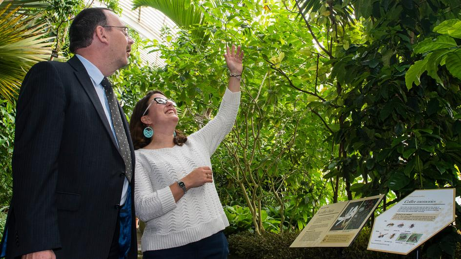 Researcher and corporate partner looking at plants