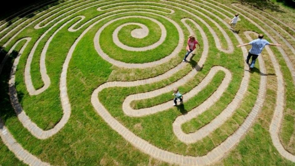 Children run through the Labyrinth at Wakehurst