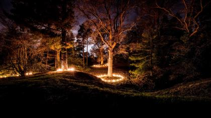 Circles of fire torches around trees at Wakehurst during Glow WIld