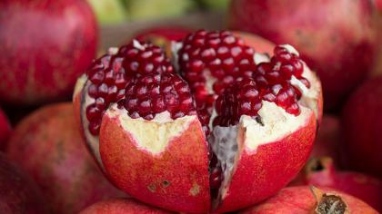 Open pomegranate (Punica granatum) fruit that is spherical and red with deep red tissue surrounding seeds