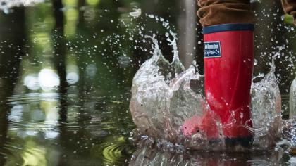 Red wellies splashing in puddle
