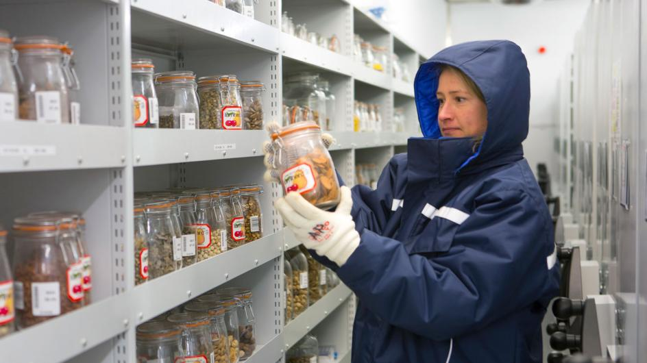 Kew scientist in coat holding jar of seeds