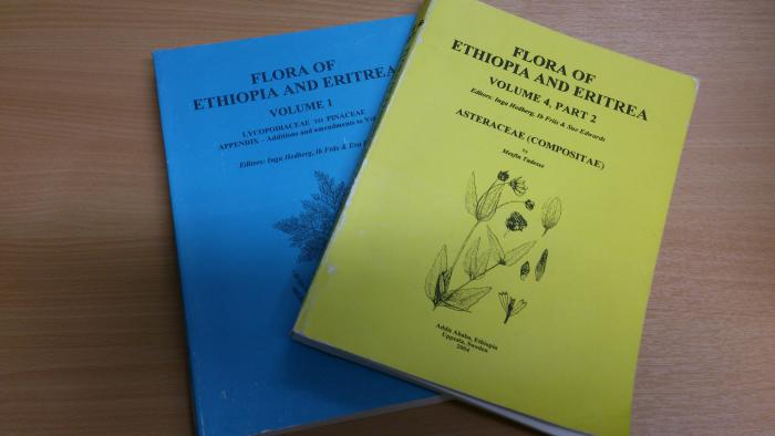 Picture shows two volumes from Flora of Ethiopia, the blue volume covers Lycopodiaceae to Pinaceae and the yellow volume covers Asteraceae